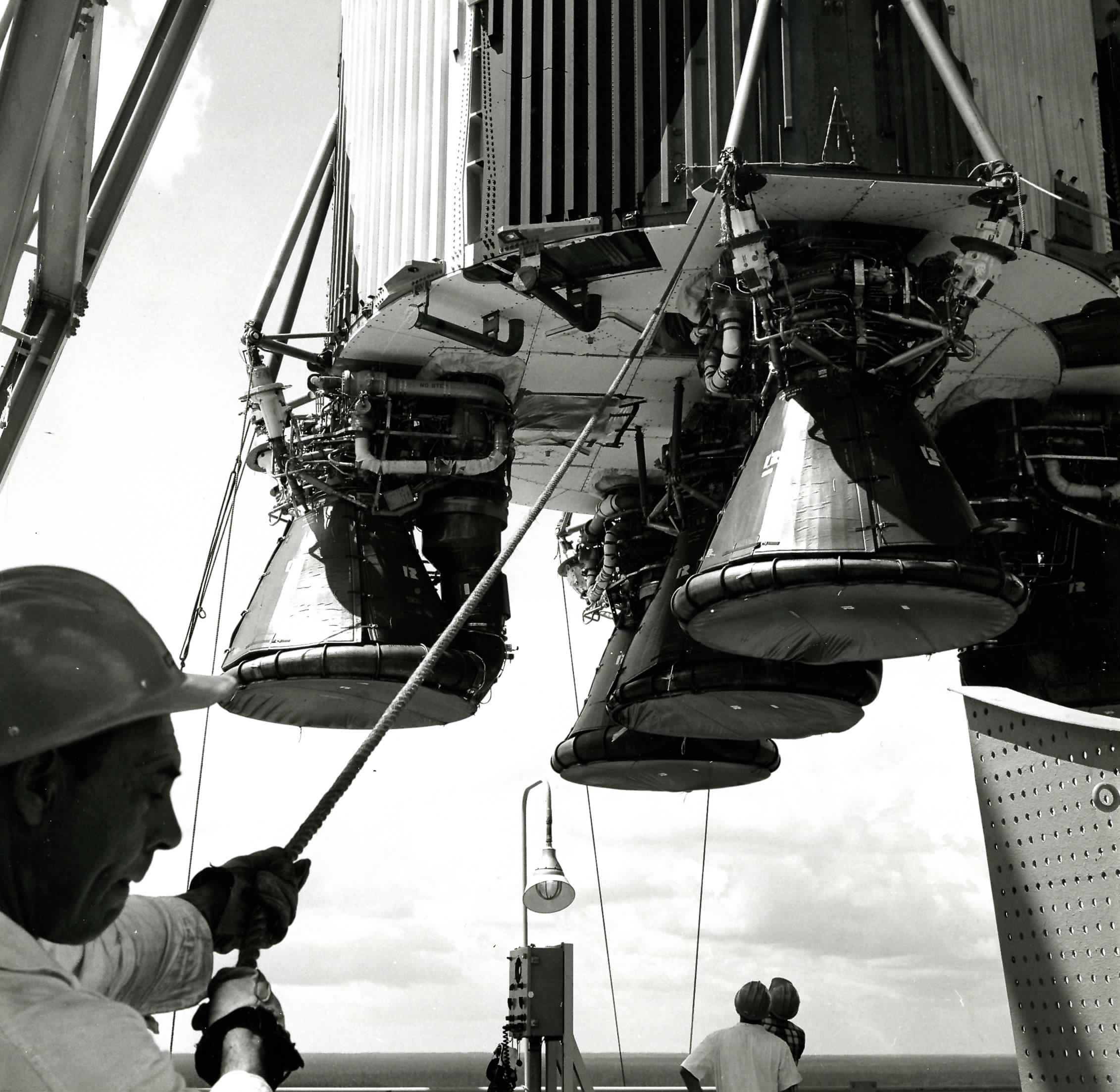F-1 on Test Stand in Mississippi – A workman holds the line on the giant S-IC first stage of the Saturn V space vehicle as it is placed into the test stand at NASA's Mississippi Test Facility – now called Stennis Space Center. The big first stage has five F-1 engines, manufactured by Aerojet Rocketdyne that were used to launch the Apollo 11 astronauts on their journey to the moon. Photo courtesy of NASA.