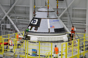 Oct. 16, 2019 - Boeing's CST-100 Starliner spacecraft's crew module is lifted onto its service module inside the Commercial Crew & Cargo Processing Facility, Kennedy Space Center, before its Orbital Flight Test. Credits: Boeing
